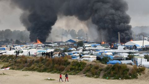 Smoke rises from multiple fires blazing in the camp on Wednesday, October 26, as French authorities work to demolish the settlement and evacuate its residents to reception centers around France.