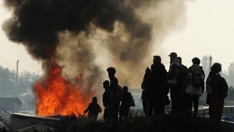Remaining migrants watch fires burn across the Jungle on October 26. Migrants set fire to structures along the camp's main street.