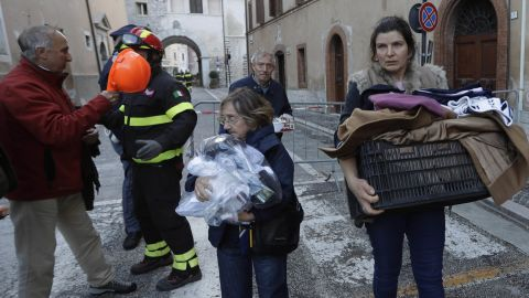 Residents carry some of their belongings through Visso.