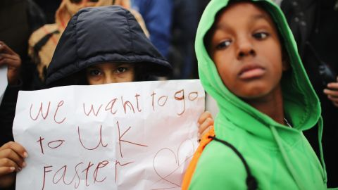 Women and children protest their case to the UK government from the Jungle, as authorities continue the destruction of the camp on October 26.