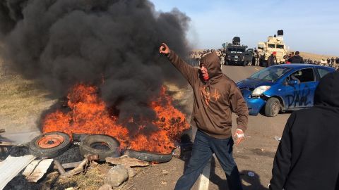 Demonstrators stand near burning tires as they face off with law enforcement Thursday.