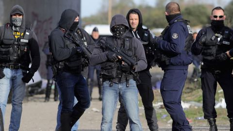 French police clear the main entrance and road into the Calais 'Jungle' migrant camp.