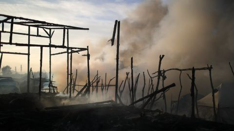 The remains of makeshift structures smolder from fires that broke out overnight in parts of the camp on October 26.