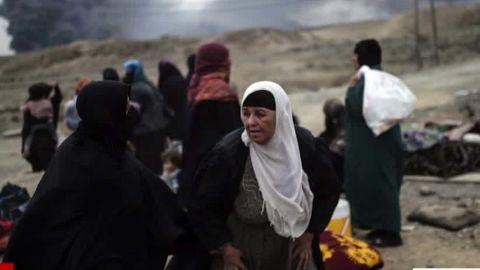 Displaced Iraqi families gather near Qayyarah on Friday.