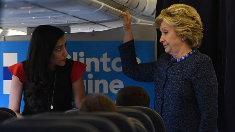US Democratic presidential nominee Hillary Clinton talks to staff onboard her campaign plane at the Westchester County Airport in White Plains, New York, on October 28, 2016.