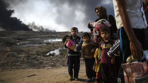 Displaced families are seen on the road near Qayyara on Saturday, October 29.