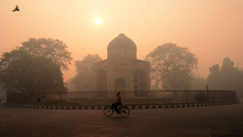 """TOPSHOT - An Indian cyclist rides along a street as smog envelops a monument in New Delhi on October 31, 2016, the day after the Diwali festival. New Delhi was shrouded in a thick blanket of toxic smog a day after millions of Indians lit firecrackers to mark the Diwali festival, causing the air pollution to hit """"severe"""" level. The pollutants breached the 1000 microgram mark in the Indian capital and shot up nearly 10 times above the normal level in  the early hours of Monday, mostly owing to bursting of millions of firecrackers, according to a weather scientist.  / AFP / MONEY SHARMA        (Photo credit should read MONEY SHARMA/AFP/Getty Images)"""