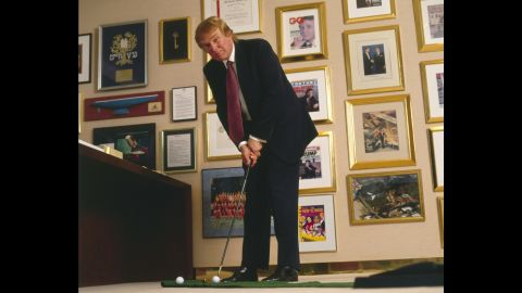 Trump putts a golf ball in his New York office in 1998.