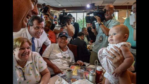 """A baby looks at Maryland Gov. Larry Hogan at a diner in Annapolis, Maryland, on July 15, 2015. Hogan was there to endorse Republican presidential candidate Chris Christie, at left in the blue tie. Christie <a href=""""http://www.cnn.com/2015/06/30/politics/chris-christie-2016-presidential-campaign/"""" target=""""_blank"""">joined the race</a> with strong national name recognition and a record in public office that spans more than a decade, having served as New Jersey's governor since 2010 and a U.S. Attorney from 2002-2010."""