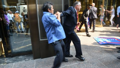 """Keith Schiller, Trump's director of security and longtime bodyguard, holds back demonstrator Efrain Galicia at Trump Tower in New York on September 3, 2015. Galicia was among five protesters who later <a href=""""http://www.cnn.com/2015/09/09/politics/donald-trump-protesters-lawsuit/index.html"""" target=""""_blank"""">filed a lawsuit</a> against Schiller, Trump, Trump's campaign and his company. The plaintiffs allege that Trump security officials, namely Schiller, assaulted them as they protested outside of a campaign event. A campaign spokesperson <a href=""""https://www.washingtonpost.com/politics/trump-security-detail-makes-headlines-just-like-the-candidate/2015/09/04/1b2333ce-5335-11e5-933e-7d06c647a395_story.html"""" target=""""_blank"""" target=""""_blank"""">told The Washington Post</a> that the protesters """"were harassing people on the street"""" and that a Trump security guard was """"jumped from behind."""""""