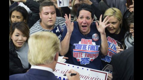 A supporter reacts as Trump signs her poster during a campaign rally in Lowell, Massachusetts, on January 4, 2016.