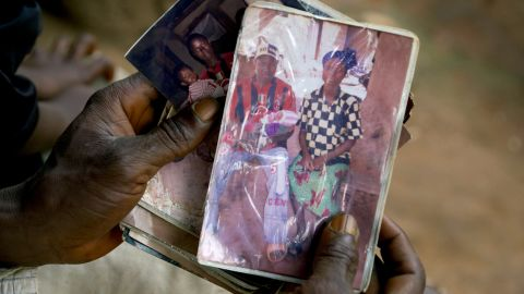 """Emile Ouamouno, a 2-year-old boy in the southern Guinea village of Meliandou, was identified as """"patient zero"""" in the Ebola outbreak circa 2014. Emile died of the disease, as did several of his family members. Emile's father, Etienne Ouamouno, holds a picture of his second wife, Sia Dembadouno, and Emile."""