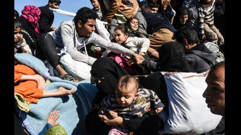 Iraqi families pack into a truck to be moved to camps on Thursday, November 3.