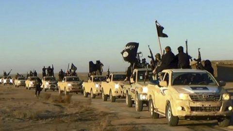 FILE - In this undated file photo released by a militant website, which has been verified and is consistent with other AP reporting, militants of the Islamic State group hold up their weapons and wave flags on their vehicles in a convoy on a road leading to Iraq, while riding in Raqqa, Syria. Simultaneous attacks on the Islamic State-held city of Mosul in Iraq and Raqqa, the de facto IS capital across the border in eastern Syria, would make military sense: They would make it harder for the extremists to move reinforcements and deny them a safe haven. (Militant website via AP, File)