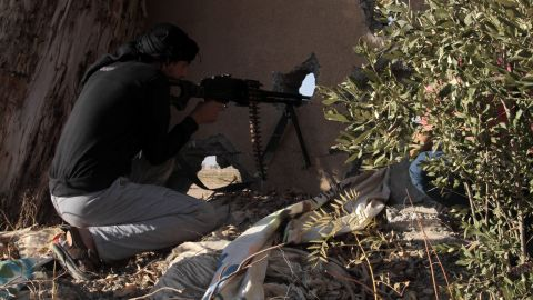 An opposition fighter holds position in clashes with government forces in the rebel-held Syrian city of Raqqa.