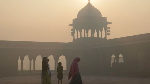 Indian women walk as smog envelops the Jama Masjid Mosque in the old quarters of New Delhi on November 3.
