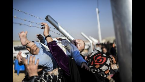 A baby is passed through a fence back to his mother at a refugee camp in the Khazir region on Saturday, November 5.