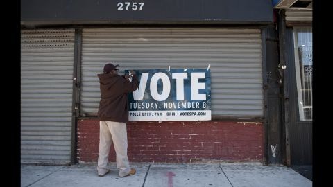 A man hangs a sign reminding people to vote in Philadelphia, Pennsylvania.
