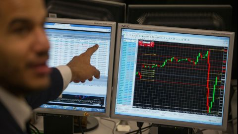 """A stock trader at ETX Capital in London gestures to a screen showing the S&P 500 Index on November 9. <a href=""""http://money.cnn.com/2016/11/08/investing/global-markets-stocks-trump-clinton-us-presidential-election/"""" target=""""_blank"""">Global stock markets dropped</a> as Trump's victory became more likely on Election Day."""
