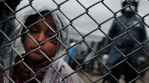 MITILINI, GREECE - OCTOBER 23: A child waits with her father at the migrant processing center at the increasingly overwhelmed Moria camp on the island of Lesbos on October 23, 2015 in Mytilene, Greece. Dozens of rafts and boats are still making the journey daily as thousands flee conflict in Iraq, Syria, Afghanistan and other countries. More than 500,000 migrants have entered Europe so far this year. Of that number four-fifths of have paid to be smuggled by sea to Greece from Turkey, the main transit route into the EU. Nearly all of those entering Greece on a boat from Turkey are from the war zones of Syria, Iraq and Afghanistan. (Photo by Spencer Platt/Getty Images)