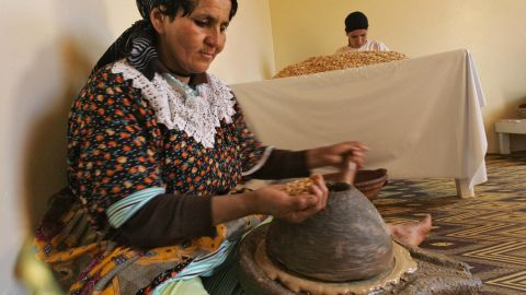 After cracking open the nut, women grind the kernels into a peanut butter-like paste.