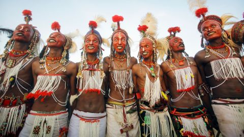 """At the end of the rainy season near Lake Chad, northern Niger, Wodaabe people come together for <em>Cure Salee</em>, the """"Festival of Nomads."""" At the center of celebrations is <em>Gerewol</em>, a male beauty contest and courtship ritual. Young men -- traditionally herdsmen -- wear full makeup, jewelry and their finest clothes and stand in line to await inspection by female onlookers. White teeth and white eyes are highly prized, so participants will grin broadly and pull all manner of expressions in the hope of attracting attention. It's flirtation <em>en masse</em>, in the hope of winning a night of passion with one of the judges."""