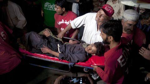 Pakistani rescue workers carry an injured victim of a bomb blast at a Sufi shrine near Karachi, Pakistan, on November 12, 2016.