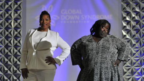 """Queen Latifah walks the runway with DeOndra Dixon during the 2016 Global Down Syndrome Foundation """"Be Beautiful, Be Yourself"""" fashion show."""