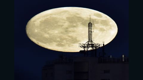 """The moon rises over a building in Madrid on November 13, 2016, on the eve of the """"supermoon."""""""