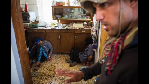 A member of Iraq's special forces guards two suspected ISIS fighters found hiding in a house in Mosul on November 11.