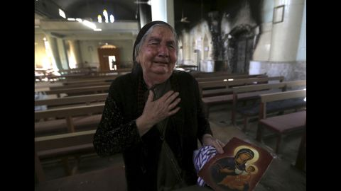 A woman cries Sunday, November 13, after seeing the St. Addai church that was damaged by ISIS fighters during their occupation of the Keramlis village.