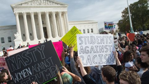 Students hold signs in front of the Supreme Court in Washington during a protest on Tuesday, November 15.