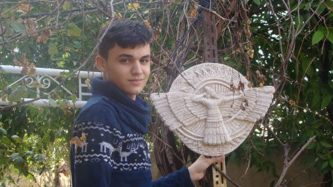 Thabit holds a picture of Ashur, a primary Assyrian deity and the god of war