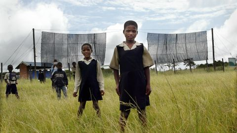 Two nets are used to collect fog and produce water for the village of Taleni in Eastern Cape, South Africa. Pictured here, school pupils from Nomvalo stand in front of the nets in March 2006.