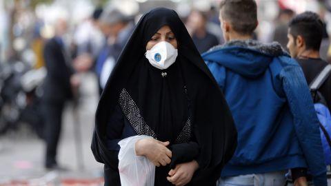 An Iranian woman wears mask as she walk in a street in Tehran on November 16, 2016.