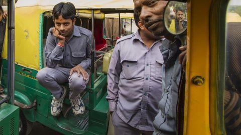 Sarvesh sitting on his auto rickshaw.