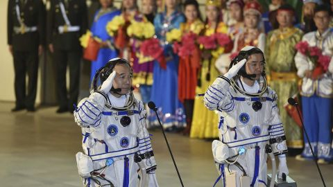 Chinese astronauts Jing Haipeng (L) and Chen Dong salute during the send-off ceremony of the Shenzhou-11 manned space mission at the Jiuquan Satellite Launch Center in Jiuquan, China.