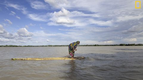 """Photo: Probal Rashid. """"A flood-affected woman on a raft approaches a boat, searching a dry place to shelter herself in Islampur, Jamalpur, Bangladesh. Bangladesh is one of the countries most vulnerable to the effects of climate change,"""" wrote Rashid. <em>Via National Geographic Your Shot</em>"""