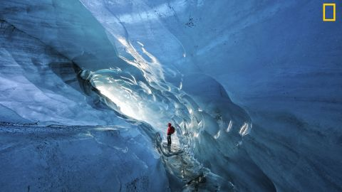"""Photo: Tom Schifanella, USA: """"Since 2000, Icelandic glaciers have lost 12% of their size, in less than 15 years. Pictured here, Icelandic guide Hanna Pétursdóttir admires an ice cave inside the Svínafellsjökull Glacier, which she notes is rapidly expanding due to the effects of global warming,"""" wrote Schifanella. <em>Via National Geographic Your Shot</em>"""