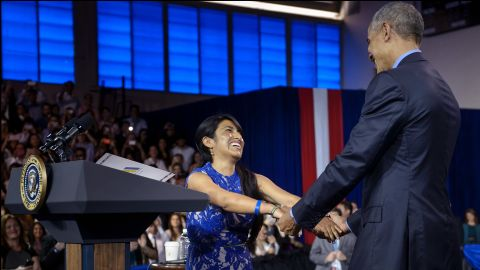 Cyntia Paytan greets Obama after introducing him at the town-hall meeting.