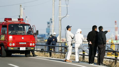 Firefighters watch the port to check the water level after a tsunami warning in Soma, Fukushima prefecture, Tuesday, November 22.