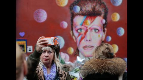 """A woman takes a selfie in front of a David Bowie mural in London on Tuesday, January 12. <a href=""""http://www.cnn.com/2016/01/11/entertainment/david-bowie-thr-obit/index.html"""" target=""""_blank"""">The rock legend died</a> January 10 at the age of 69."""