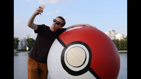 """A young man takes a selfie Tuesday, July 26, by a sphere monument that had been painted into a giant """"poke ball"""" in Yekaterinburg, Russia. The mobile game """"Pokemon Go"""" <a href=""""http://money.cnn.com/2016/07/19/investing/pokemon-go-nintendo-shares/index.html"""" target=""""_blank"""">has been a sensation</a> for its company, Nintendo."""