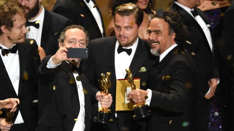 """Cinematographer Emmanuel Lubezki takes an on-stage selfie with actor Leonardo DiCaprio and director Alejandro Gonzalez Inarritu during the Academy Awards on Sunday, February 28. All three won Oscars for """"The Revenant."""""""