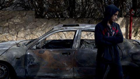 A boy stands next to a burnt car in Zikhron Ya'akov on November 23.