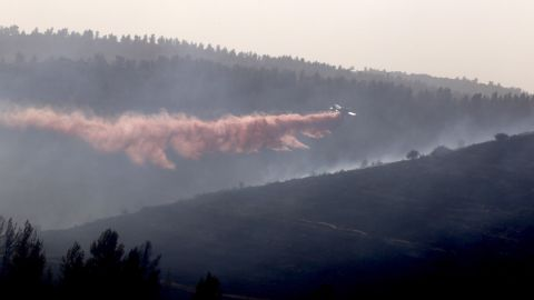 A plane drops fire retardant on wildfires in the hills near Nataf, Israel, on November 23.