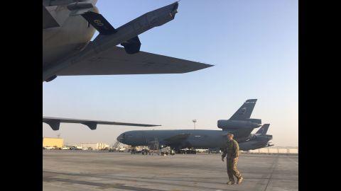 A crew member walks toward a KC 10 back on the tarmac.