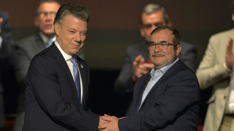 Colombian President Juan Manuel Santos and the head of the FARC, guerrilla Timoleon Jimenez, shake hands in April during the second signing of the historic peace agreement.