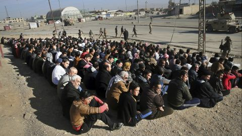 Iraqi civilians sit on the ground in Mosul on November 24. An Iraqi officer addressed the group, demanding to know the whereabouts of alleged ISIS militants who opened fire on troops a few days earlier.