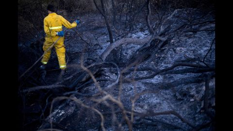 A firefighter extinguishes smoldering ashes in Zikhron Ya'akov, south of Haifa, on Wednesday, November 23.
